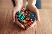 Hands full of colorful buttons. Debica, Poland