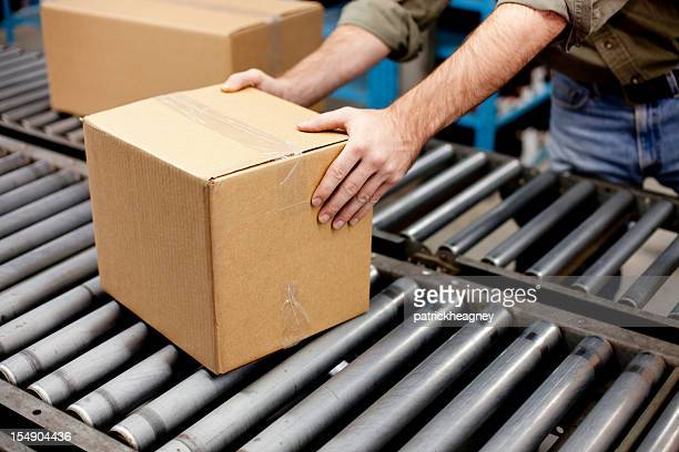 Hands getting a box off of conveyer belt