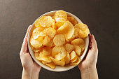 Hands giving bowl of potato chips on brown background. Concept of snack food. Top view.