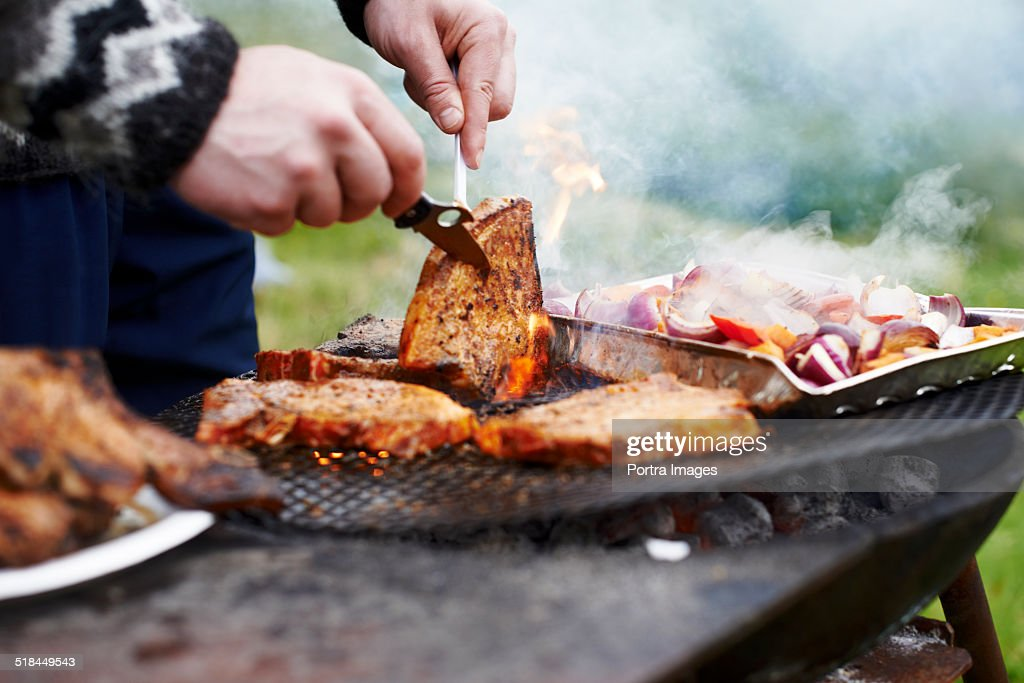 Hands grilling meat on barbecue