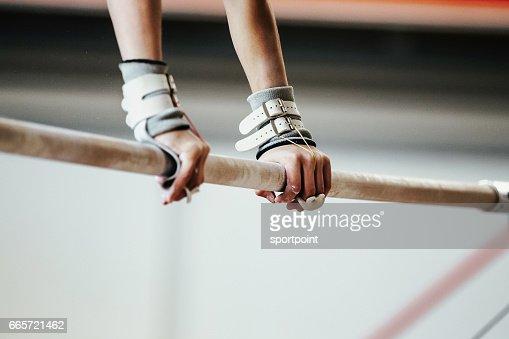hands grips athletes female gymnast exercises on uneven bars : Stock Photo