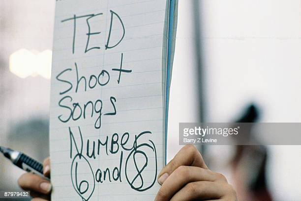 Hands hold up a sign that reads 'Ted shoot songs number 6 and 8' the Woodstock Music and Arts Fair in Bethel New York August 15 17 1969 The note...