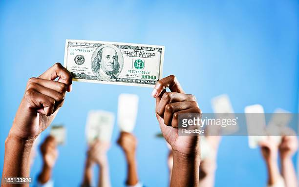 Hands hold up US $100 bill with more in background