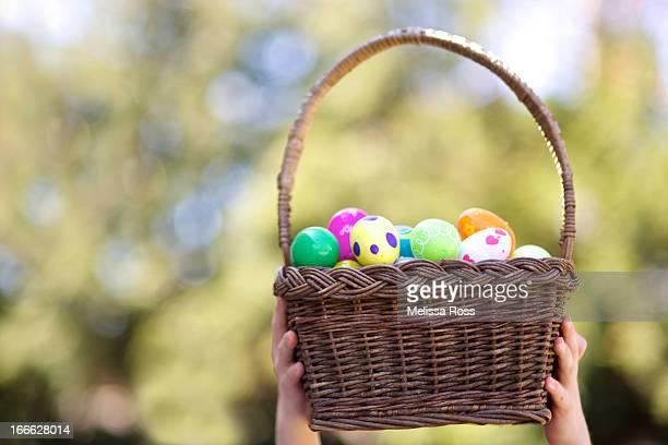 Hands holding a basket full of Easter eggs
