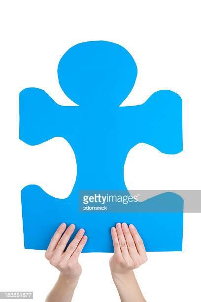 Hand hält eine blaue Puzzle Stück-Autism Awareness