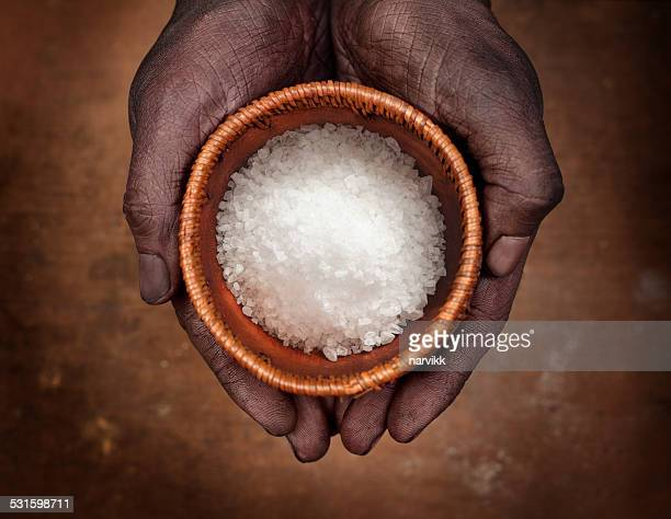 Hands holding a bowl with salt crystals