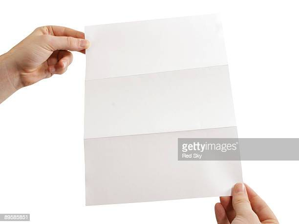 Hands holding a folded piece paper