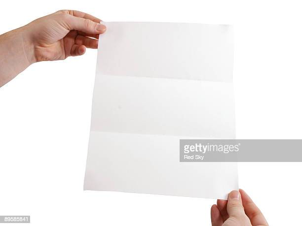 Hands holding a folded white piece of paper