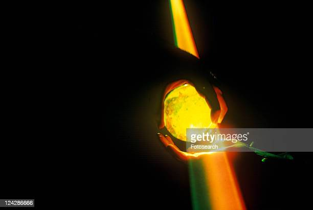Hands holding a glowing crystal sphere as orange laser light shines down