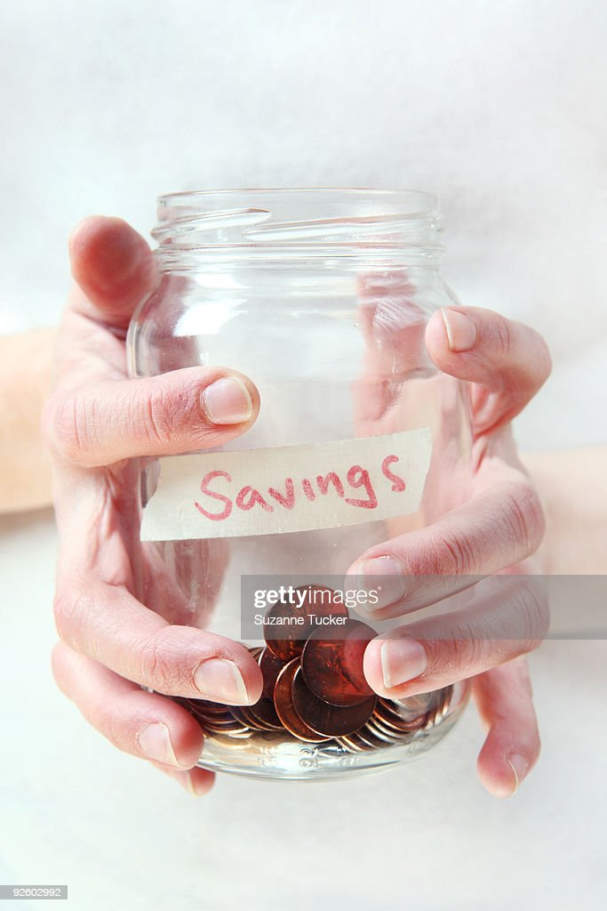 Hands holding a jar of coins : Stock Photo