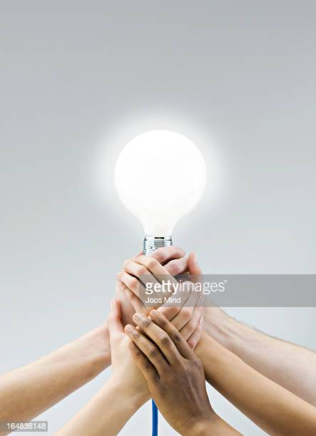 Hands holding a large light bulb