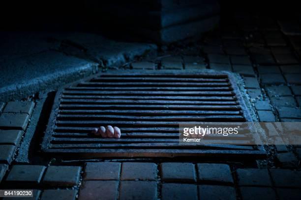 Handen met een putdeksel uit onder bij nacht