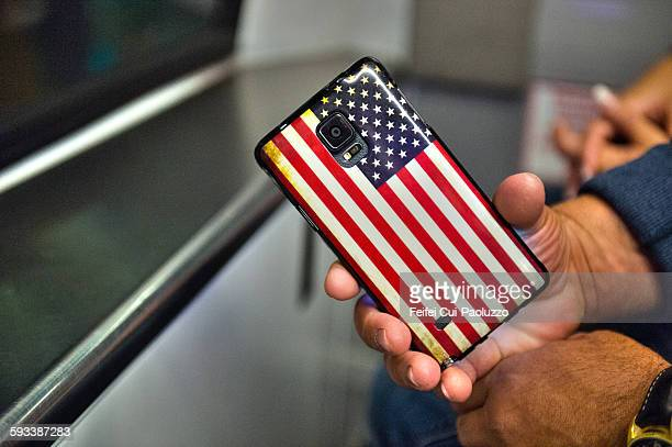Hands holding a smartphone with american flag case