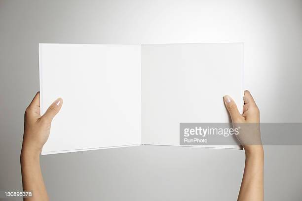 hands holding a white book,hands close-up