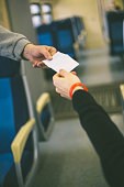 Hands holding a white ticket