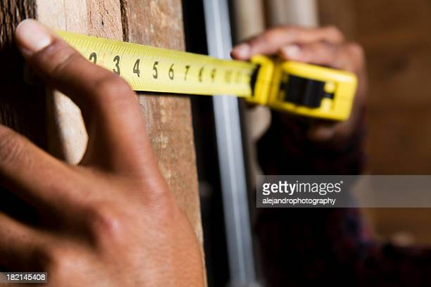 Hands holding a yellow measuring tape against a wooden wall
