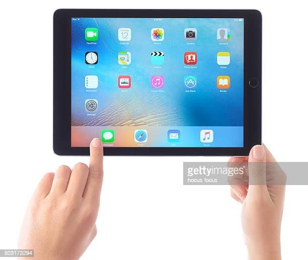 Hands holding Apple iPad Air on white