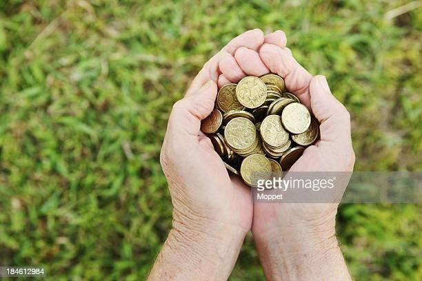 Hands holding Australian dollar coins over grass