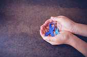 hands holding blue ribbons, toning background