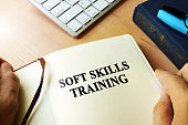 Hands holding book with title Soft skills training.