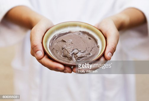 Hands holding bowl of mud skin treatment