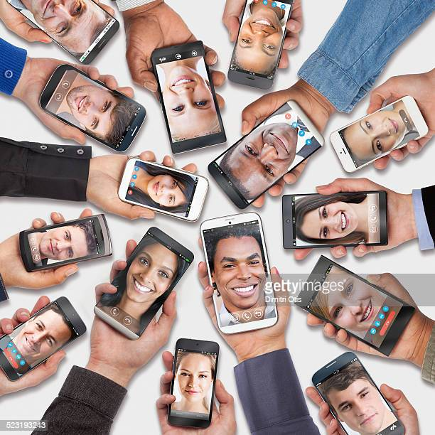 Hands holding cell phones, faces on each screen