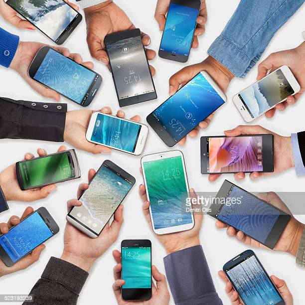 Hands holding cell phones, white background