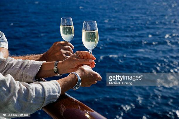 Hands holding champagne glass on cruise ship