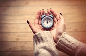 beautiful woman hands holding small blue alarm clock on the wonderful brown wooden background
