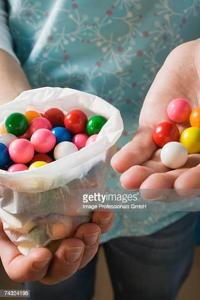 Hands holding coloured bubble gum balls