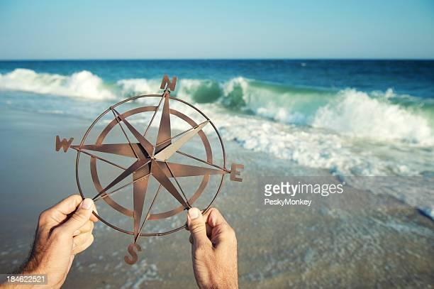 Hands Holding Compass by Sea with Crashing Waves