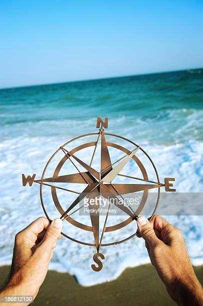 Mains tenant la boussole de la mer avec des vagues se brisant sur le rivage