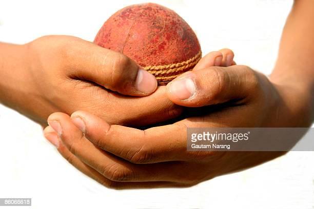Hands holding Cricket ball