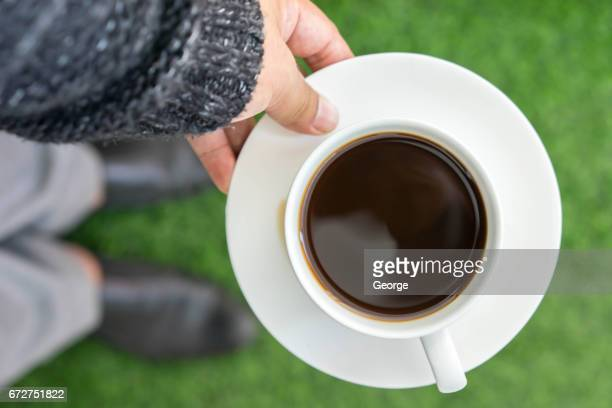 hands holding cup of coffee on grass