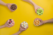 Hands holding cups with different rolled ice cream on bright yellow background, top view