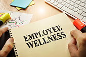 Hands holding documents with title Employee Wellness.