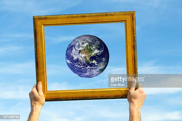 Hands Holding Earth in Frame against Blue Sky