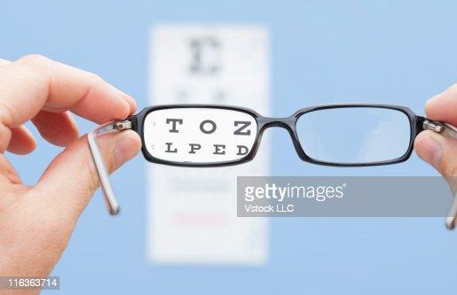 Hands holding eyeglasses in font of eye chart