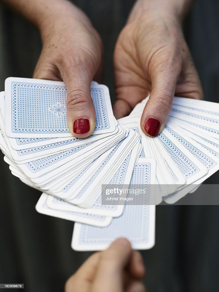 Hands holding fanned out playing cards