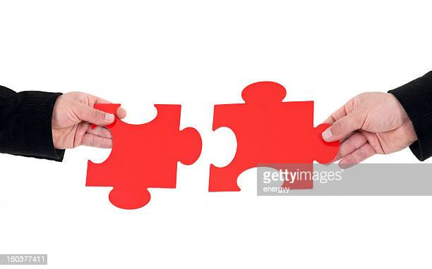 Hands holding fitting puzzle pieces before piecing together