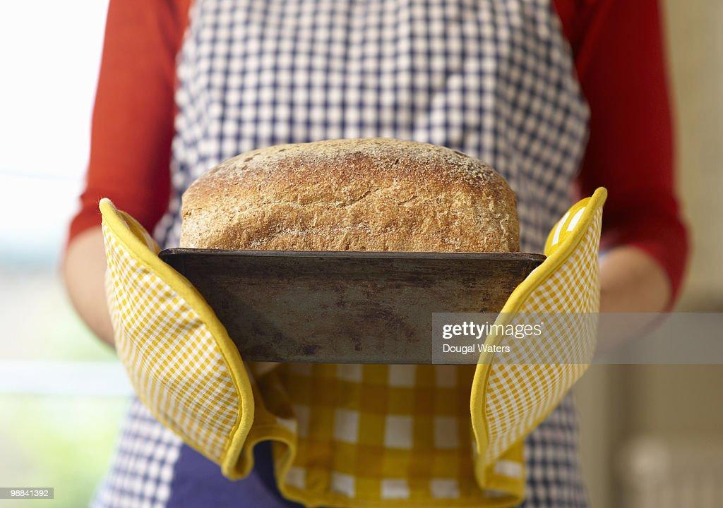 Hands holding freshly baked bread. : Stock Photo