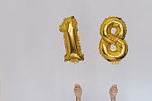Hands holding golden 18 balloons, new year concept