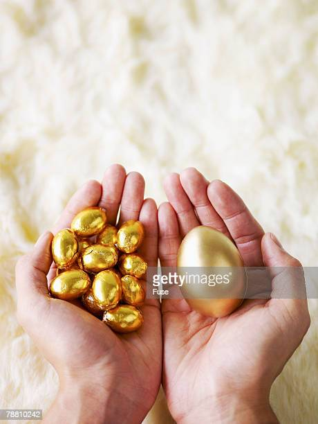 Hands Holding Golden Eggs