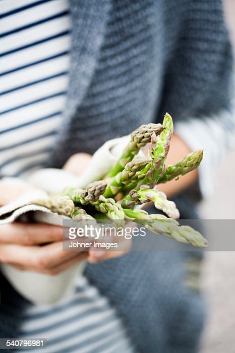 Hands holding green asparagus