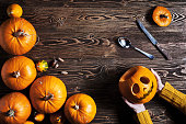 Hands holding Halloween pumpkin over wooden background, top view, flat lay with copy space for text, toned image