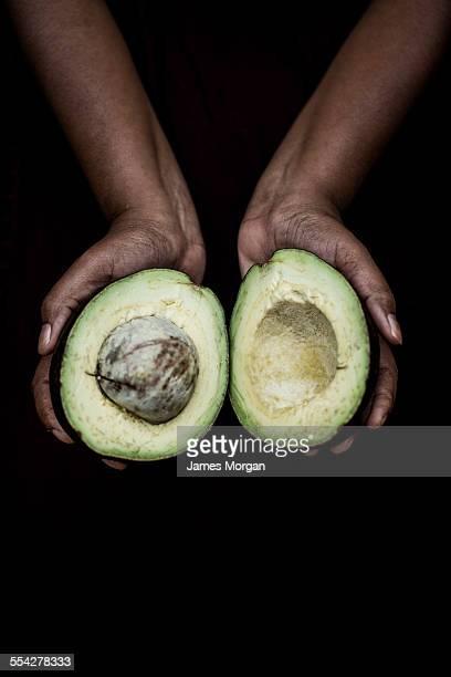 Hands holding halved avocado
