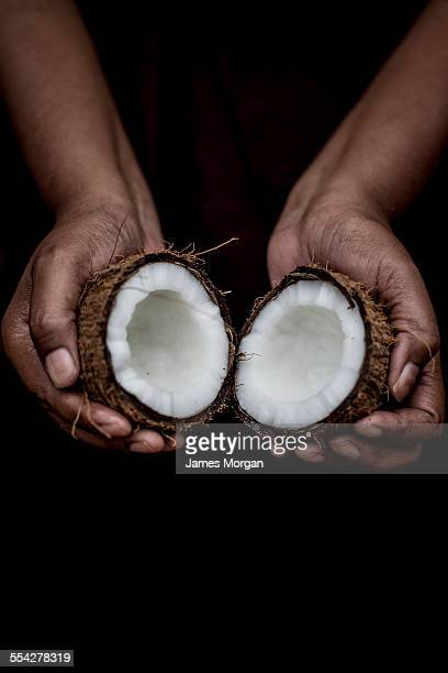 Hands holding halved coconut