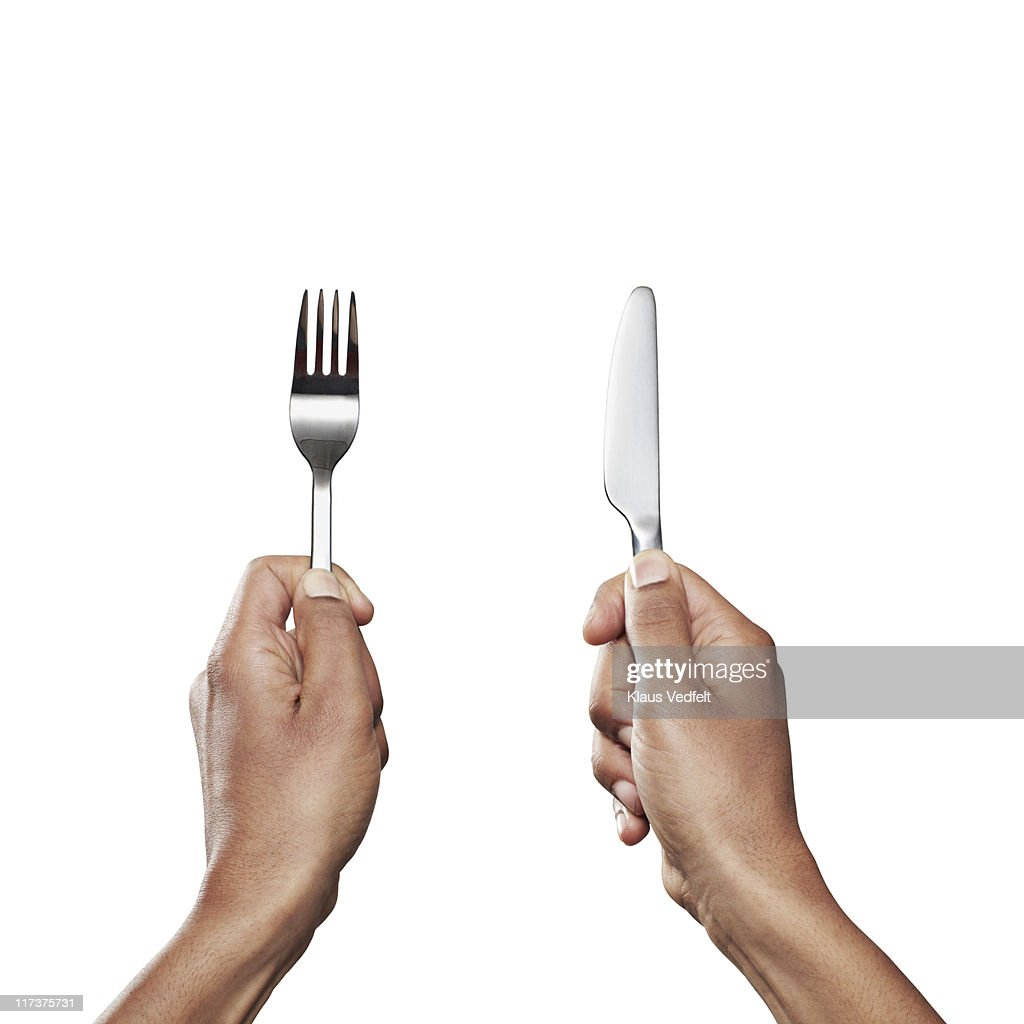 Hands holding knife and fork close-up
