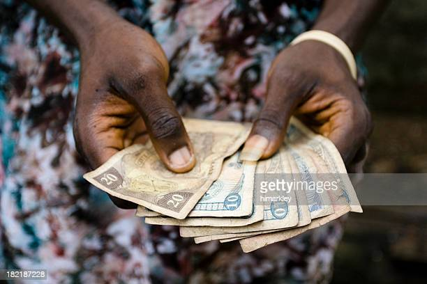 Hands holding Liberian money