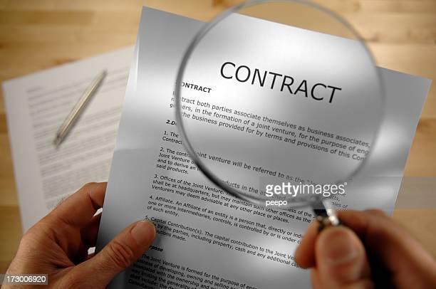 Manos sosteniendo lupa y el contrato Seleccionar imágenes